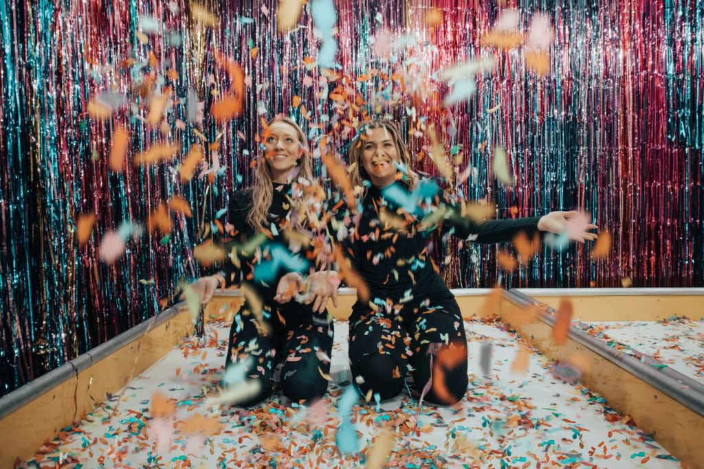 two-women-kneeling-while-throwing-confetti-1627935